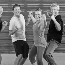 Lächelnde Senioren machen gemeinsam Piloxing im Fitnesscenter
